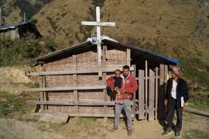 Min Badhus Tamang (t.v.), med sønnen og Ram Badhur foran landsbyens kirke.